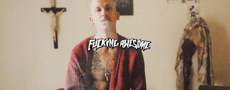 Komischer Typ, der aussieht wie Jason Dill raucht zu Hause eine Zigarette und dabei einen offenen Fucking Awesome Bademantel trägt.